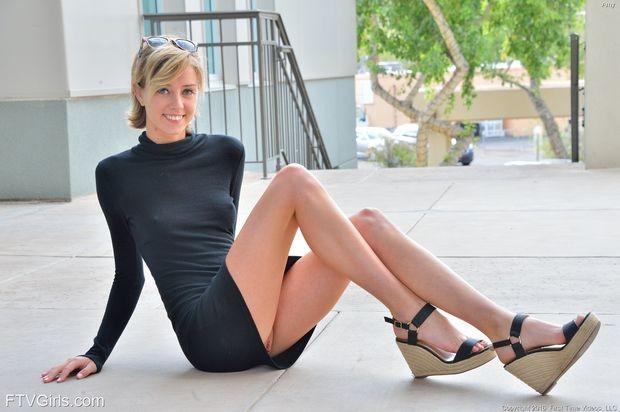 Милая блондиночка в обтягивающем черном платье без бикини