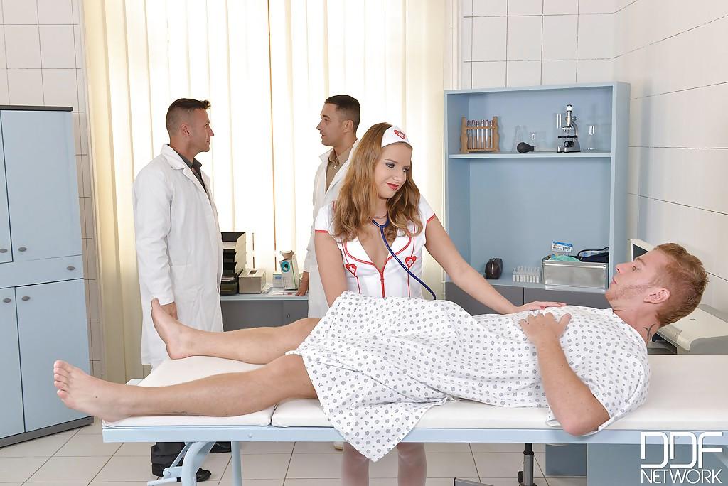 Пациент с докторами имеют голубоглазую медсестру на больничной кроватке